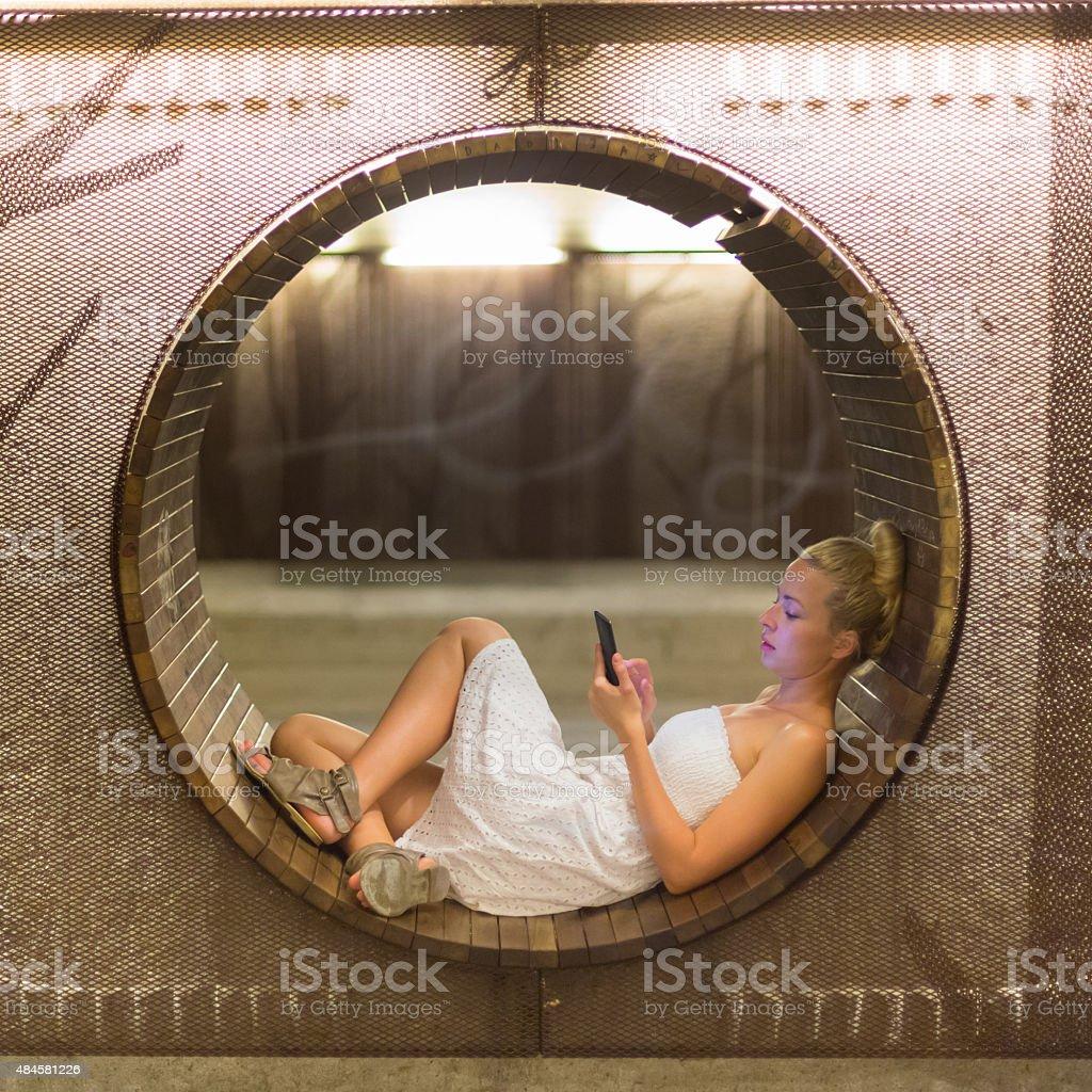 Junge Frau mit Smartphone auf Bank. Lizenzfreies stock-foto
