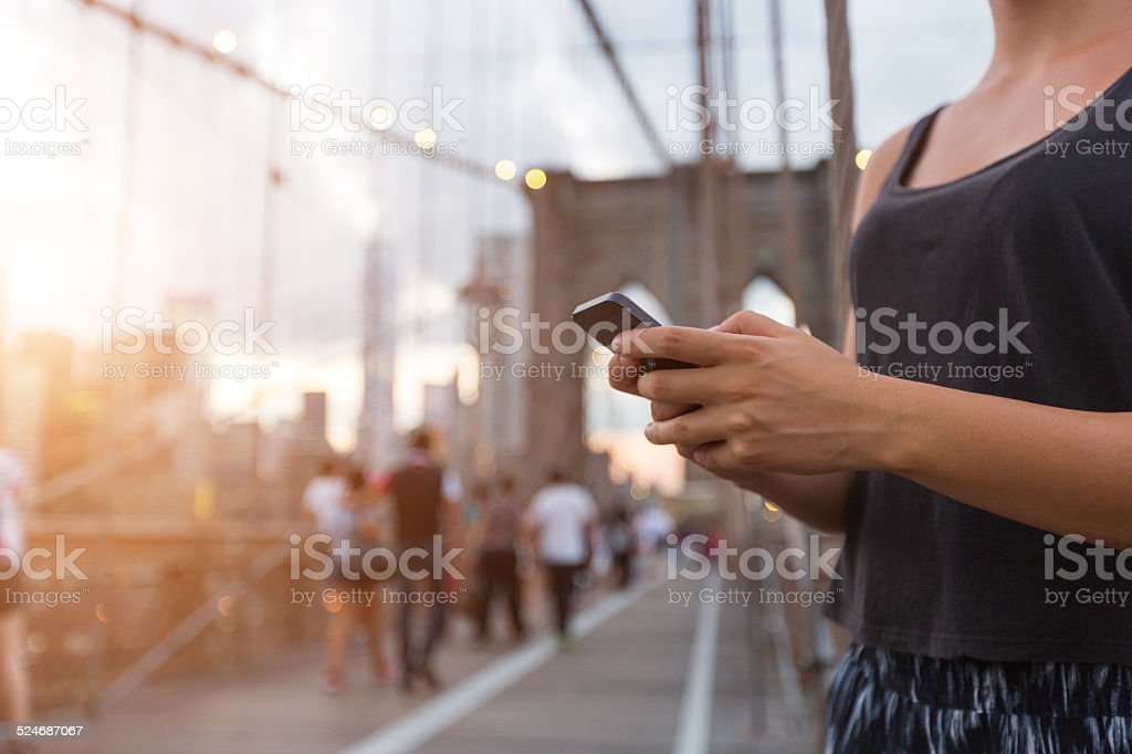 Young Woman Using Smart Phone on Brooklyn Bridge stock photo