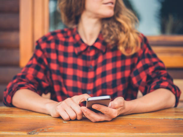 Young woman using smart phone on porch A young woman is using her smart phone on the porch of a log cabin plaid shirt stock pictures, royalty-free photos & images