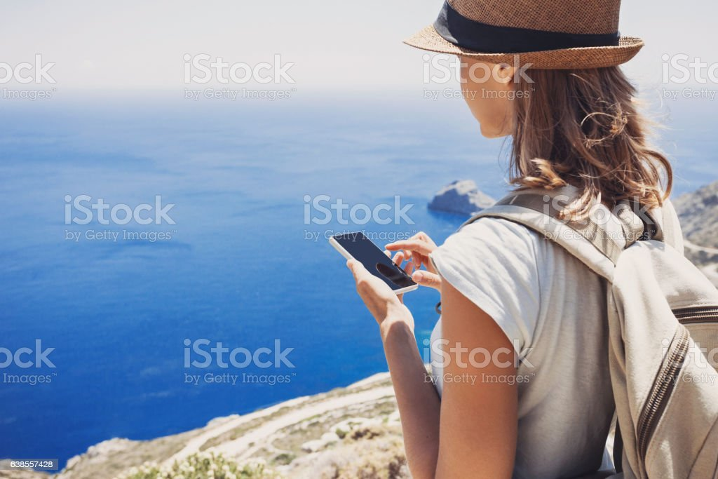 Young woman using smart phone on vacations - Photo