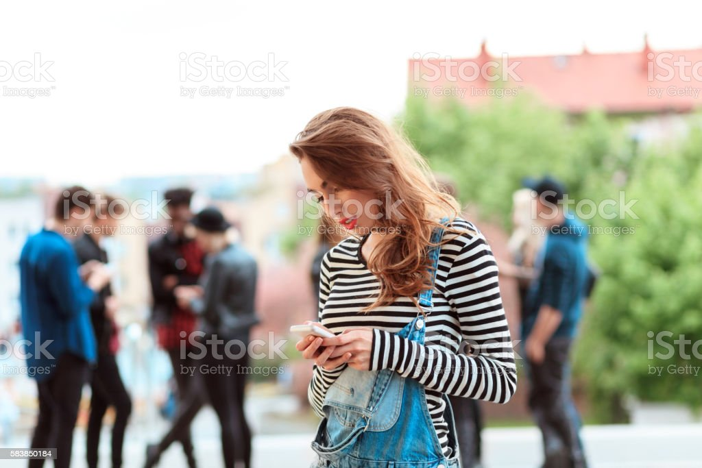 Young woman using smart phone outdoor Young woman texting on smart phone outdoor. Group of young people in the background. 20-29 Years Stock Photo