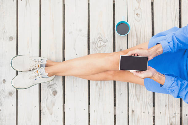 mujer joven usando teléfono inteligente  - moda de negocios informal fotografías e imágenes de stock
