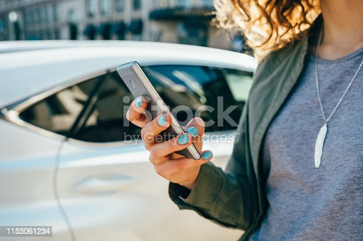 istock Young woman using smart phone standing on street 1153061234