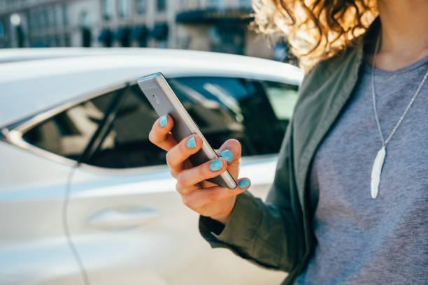 mulher nova que usa o telefone esperto que está na rua - carro mulher - fotografias e filmes do acervo