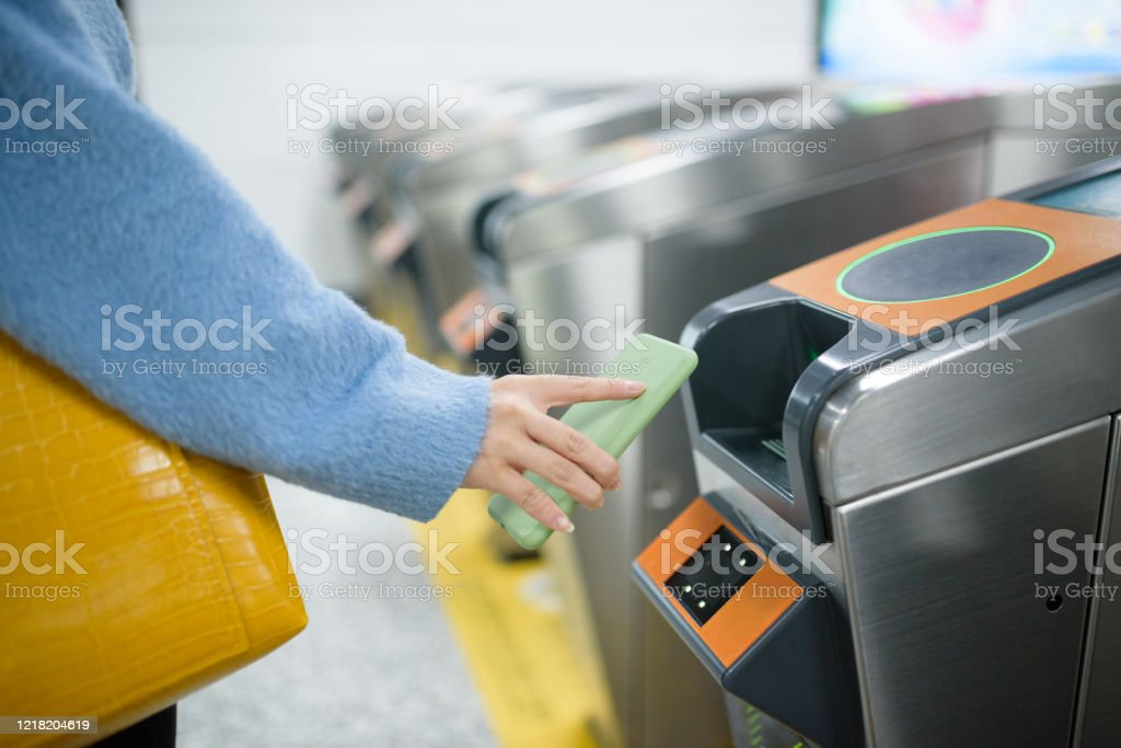 Mujer joven usando el teléfono inteligente para pagar en la estación de metro. - Foto de stock de Adulto libre de derechos