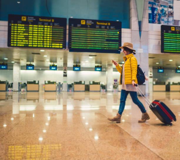 wanita muda menggunakan smartphone di terminal bandara - traveler new york potret stok, foto, & gambar bebas royalti