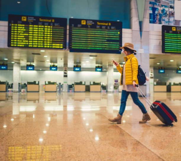 Young woman using smartphone at the airport terminal Tourist with suitcase at the airport walking and texting val d'oise stock pictures, royalty-free photos & images
