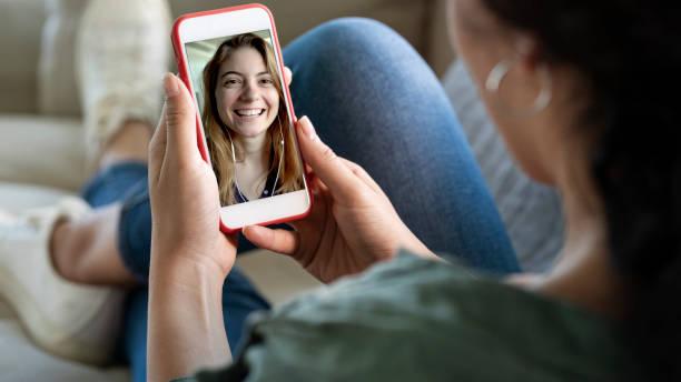 年輕女子使用智慧手機進行視頻通話 - 少女 個照片及圖片檔