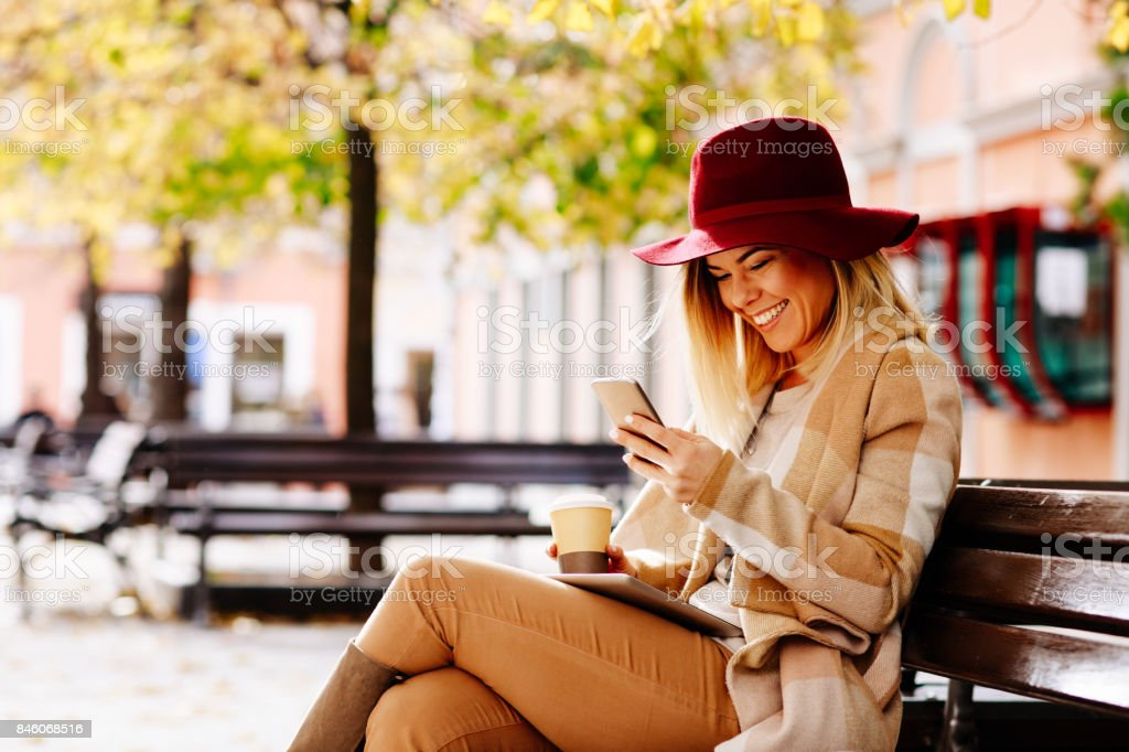 Young woman using smartphone in the city and sitting on the bench stock photo
