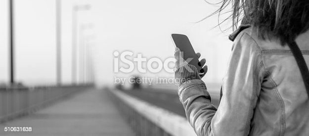 Picture of young woman standing on the bridge and using smartphone. She is wearing leather jacket.