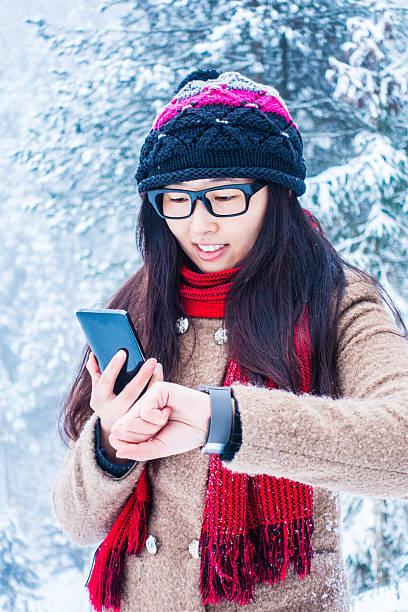 junge frau mit und smartphone im winter smash-television show - markenuhren damen stock-fotos und bilder