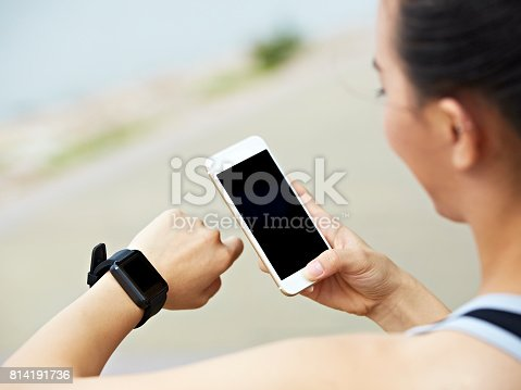 istock young woman using smartwatch and smartphone 814191736