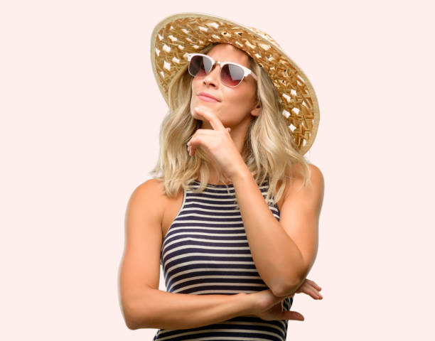 young woman using sunglasses wearing summer hat thinking and looking up expressing doubt and wonder - stupidblonde stock pictures, royalty-free photos & images