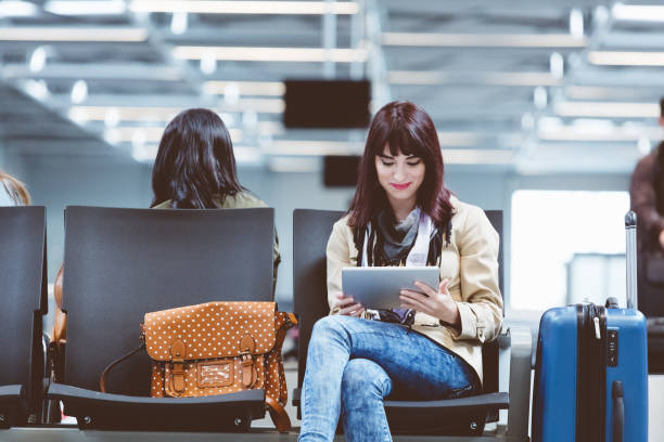 young woman using tablet pc at airport - airport terminal stock photos and pictures