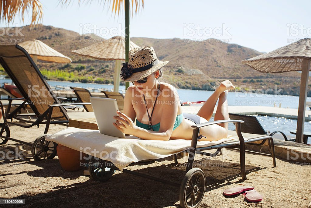 Young woman using tablet pc at the beach royalty-free stock photo