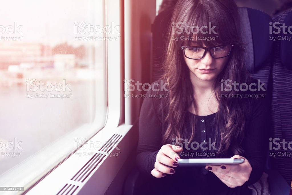 Young woman using tablet pc in train stock photo
