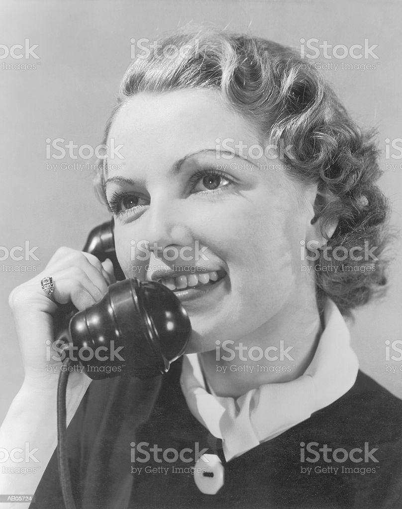 Young woman using telephone, close-up (B&W) royalty-free stock photo