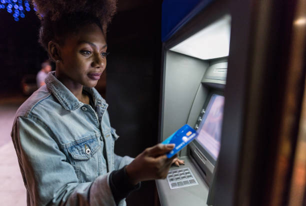 Young woman using the ATM on the street stock photo
