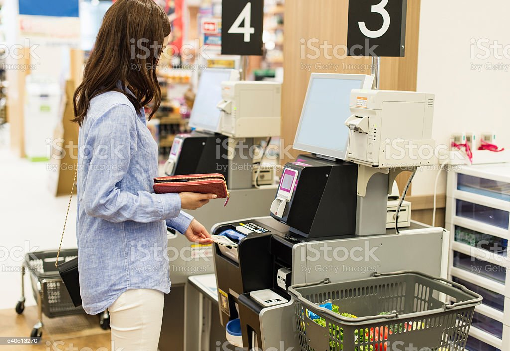 Young woman using the cash register of self-service stock photo