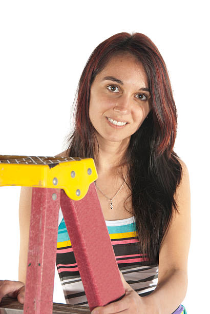 Young woman using tools and step ladder stock photo