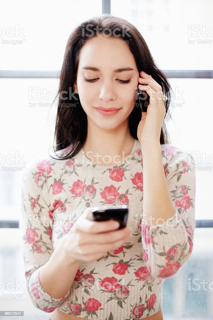 Young woman using two mobile phones - Royalty-free 25-29 Years Stock Photo
