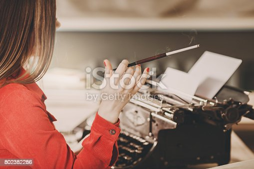 istock Young woman using typewriter. Business concepts. Retro picture style. 802382286