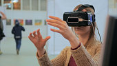 istock Young woman using virtual reality glasses 1002260796