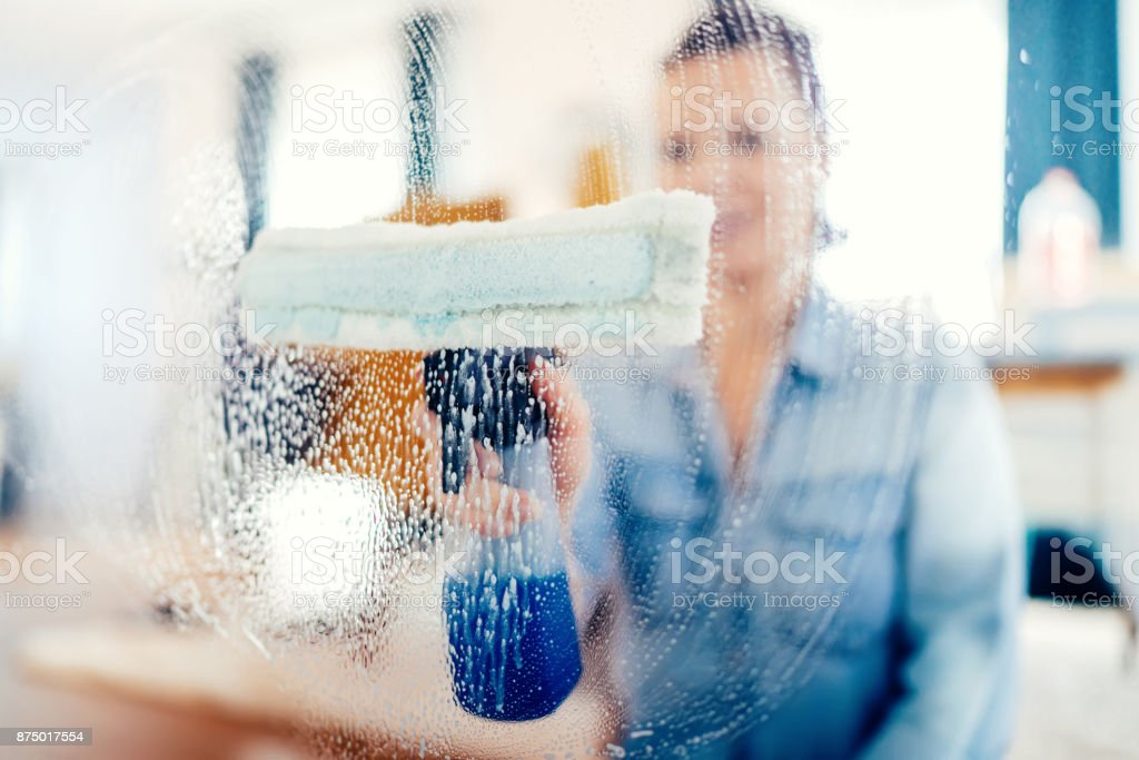 Young woman using window cleaner and doing chores around the house stock photo