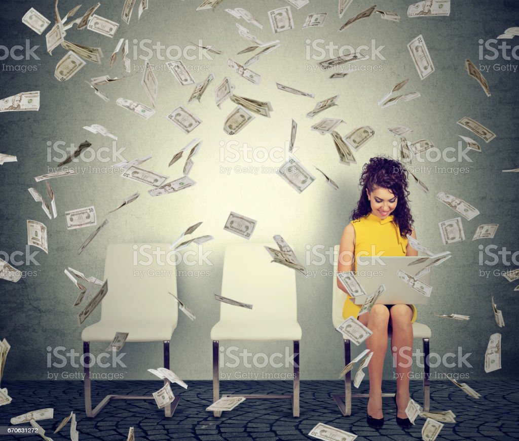 Young woman using working on a laptop building online business making money cash falling down. - foto stock
