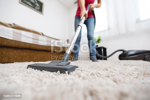 Young woman using vacuum cleaner to clean the house