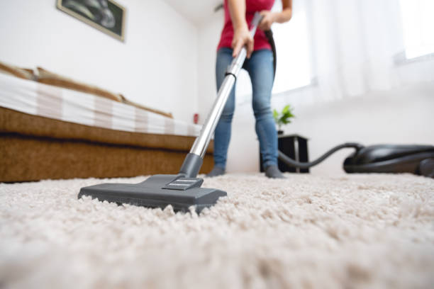 Young woman vacuuming house stock photo