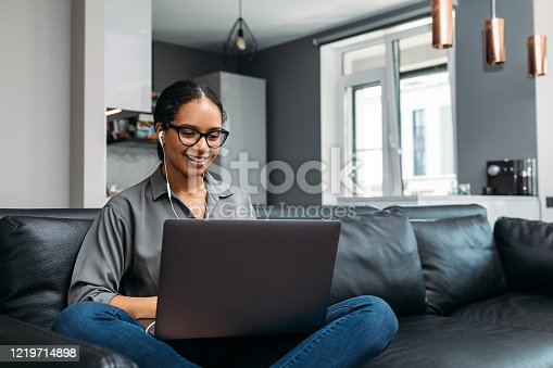 Young woman video calling using a laptop sitting on a sofa wearing earphones