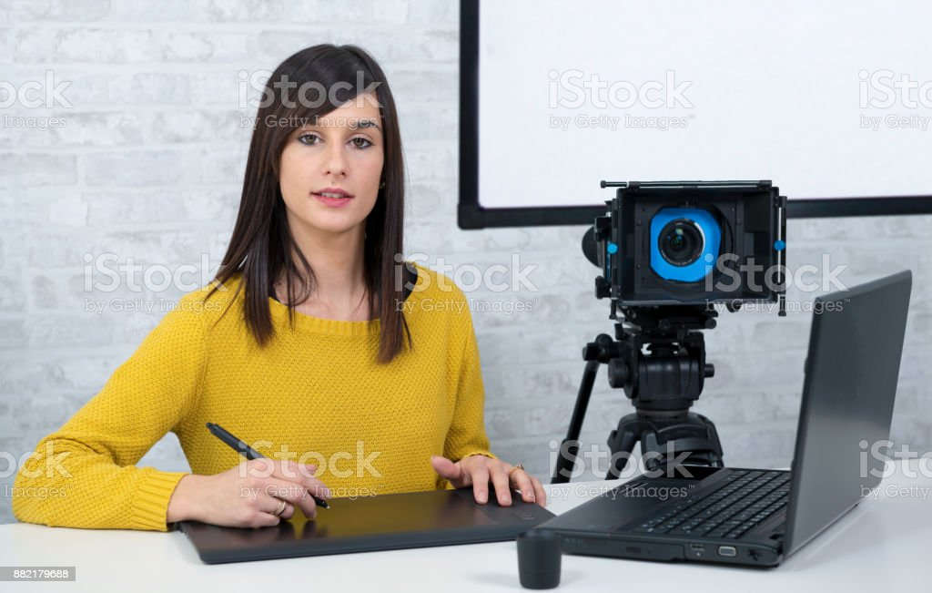 young woman videographer using graphics tablet for video editing stock photo