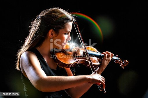 Young woman playing violing during night presentation or concert. Classical Musician.