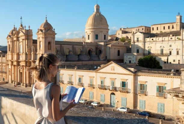jonge vrouw een bezoek aan de kathedraal van noto in sicilië, italië - noto sicilië stockfoto's en -beelden