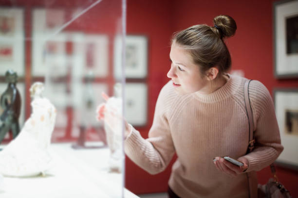Young woman visitor using  phone  in museum stock photo