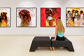 In a exhibition centre, lonely young woman visits an art exhibition and watches artist's collection on the wall. Exhibition's concept is \