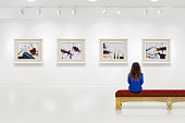 In a exhibition centre, lonely young woman visits an art exhibition and watches artist's collection on the wall. Lightened white wall contains four white frames with artist's painting.