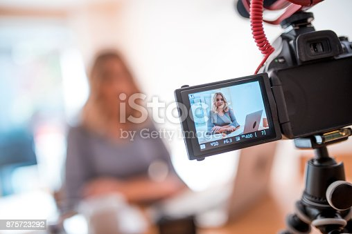 Young woman is vlogging about her business career. She is using home video camera and laptop.