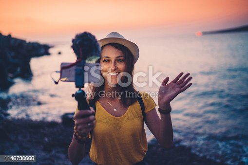 Young influencer vlogging from the seaside at sunset