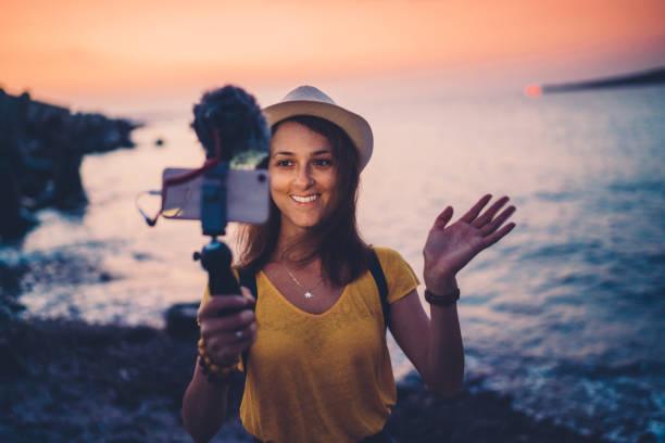 年輕女子從海灘假期的伐木 - influencer 個照片及圖片檔