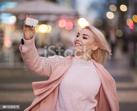 Young woman vlogging outdoors with action cam