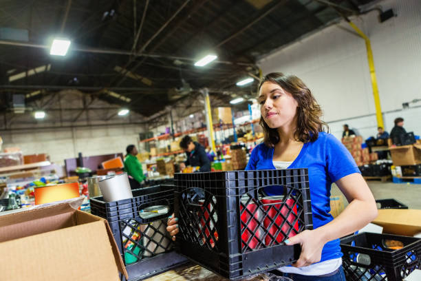 Young woman volunteering to organize donations in large food bank stock photo
