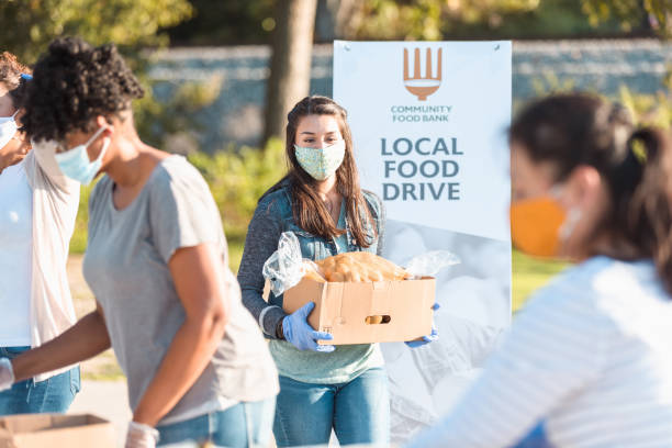 Young woman volunteers at food drive during COVID-19 stock photo