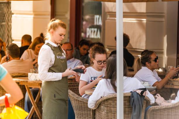 O empregado de mesa da mulher nova toma uma ordem em um café-pizzaria da rua - foto de acervo