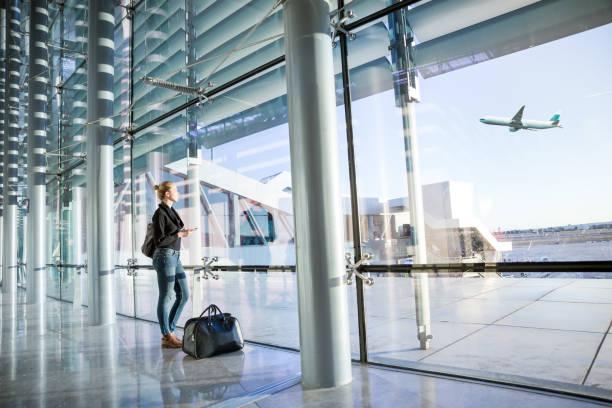 Joven esperando en el aeropuerto, mirando a través de la ventana de la puerta. - foto de stock