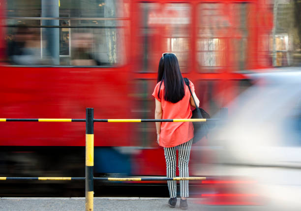 young woman waiting at bus stop and city traffic  in motion blur - stop motion stock photos and pictures
