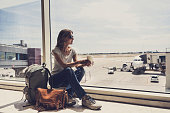Young girl waiting for a plane in the airport. Active lifestyle, tourism, vacations and travel concept