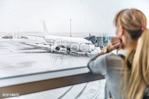 469824732istockphoto Young woman waiting for boarding 973116870