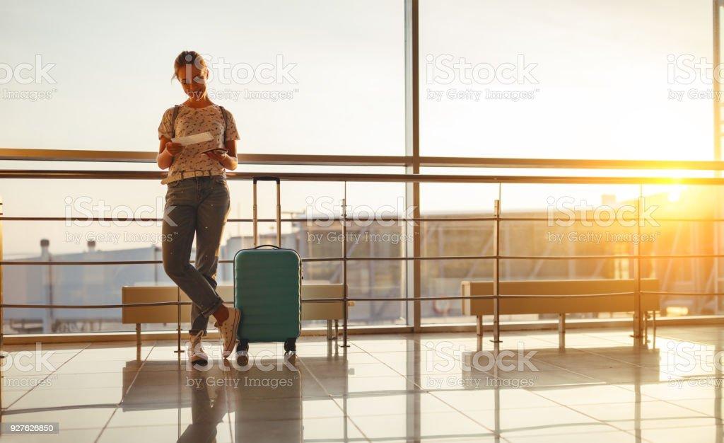 junge Frau wartet auf fliegen am Flughafen am Fenster mit Koffer – Foto
